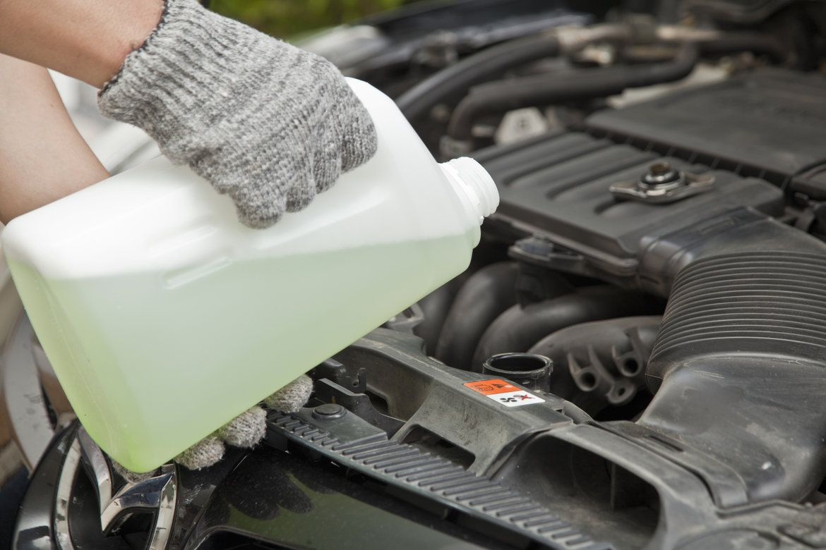 Man with gloves on and an open hood changing coolant for his car engine