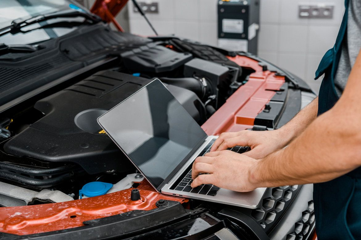 Car in a garage service shop with mechanic working on the laptop for data entry regarding maintenance tasks
