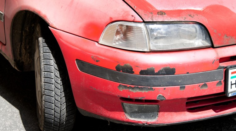 Red car with damaged exterior paint because of rust