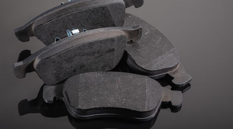 4 brake pads sitting on a shiny black surface