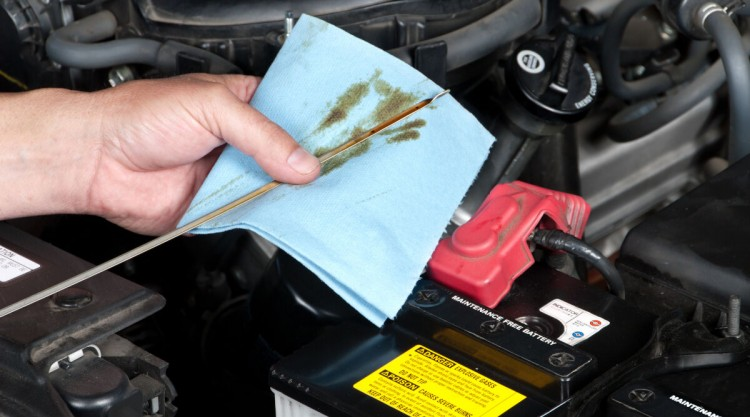 A mechanic checking engine oil levels, wiping off the dipstick