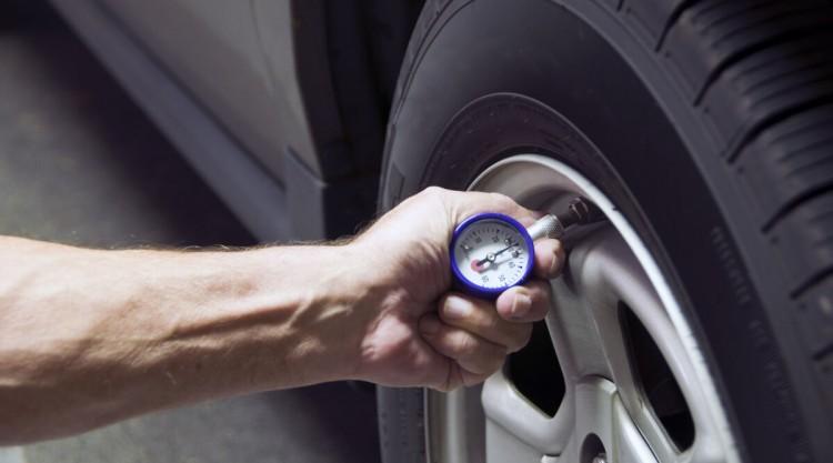 A mans hand pressing a tire pressure gauge onto a car tire