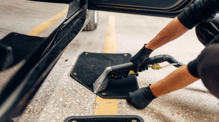 Man cleaning car mats with a steam cleaner or vacuum
