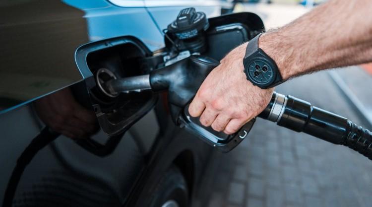 Man wearing black watch pumping his own gas in his black car