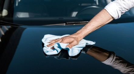 Man wiping his car's surface with a towel after finishing removing swirl marks