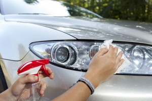 Wiping a car's headlights and completing the tree sap removal process with cloth and spray