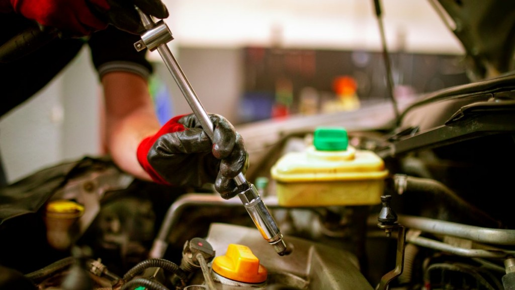 A garage employee holding a rathcet changing spark plugs in an engine