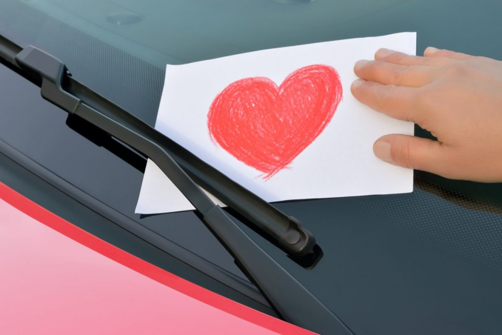 A love heart post it note being placed under wiper blades.