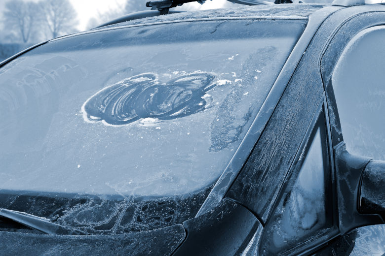 A heavily frosted windshield of a black car in winter