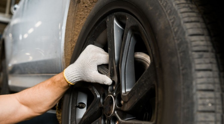 Gloved mechanic hand inspecting a car tire on a black wheel