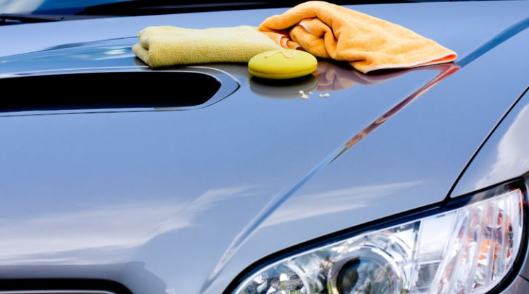 Car cleaning products on the bonnet of a shiny silver car