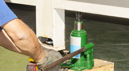 A man using a hydraulic bottle jack to lift what looks like a shipping container