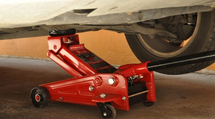 Close up of a red hydraulic floor jack lifting up a car