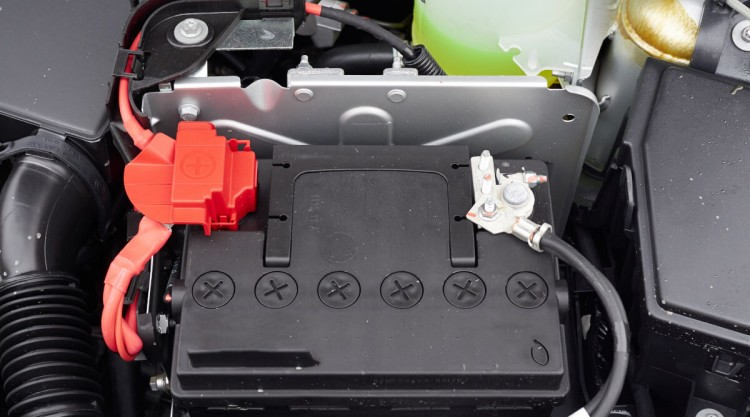 Close up of a car battery in a car with hood up