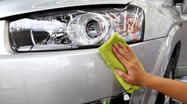 shining the headlights on a detailed silver car with a green cloth