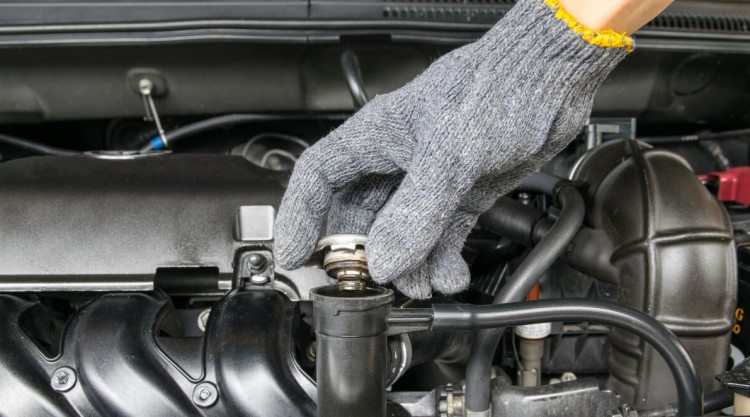 A gloved hand removing the radiator cap in a car engine
