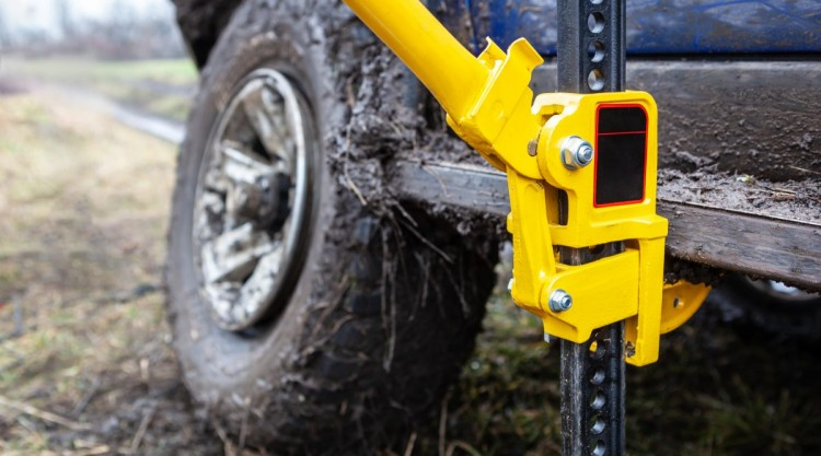 A bright yellow high lift jack being used to raise a 4x4 out of the mud