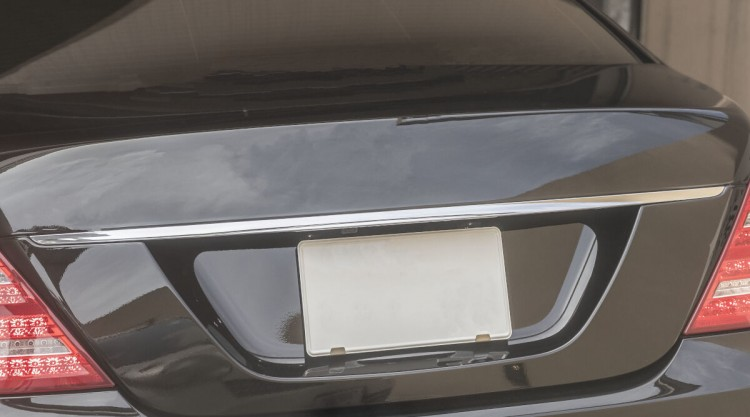 Close up of blank license plate frame on a black saloon type car