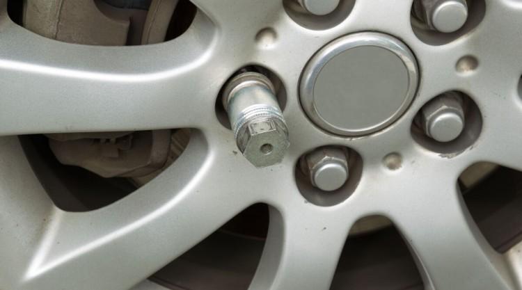 Close up of a locking lug nut on a car wheel