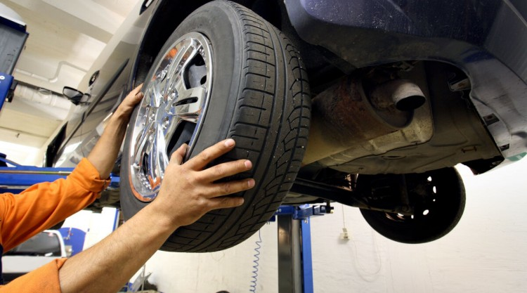 A man removing a tire from a car in the air so he can rotate the tires