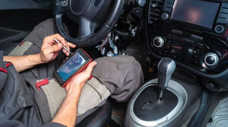 a mechanic reading codes from an OBD2 scan tool while sitting in a car