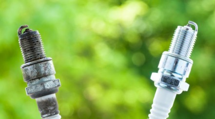 One used and one new spark plug side by side against a green background