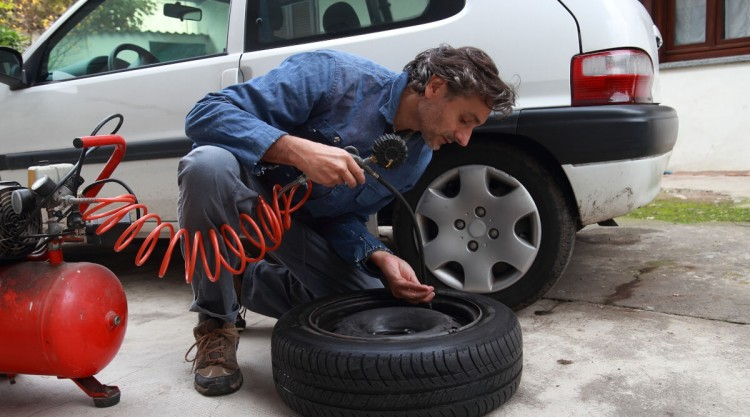 Man working with air compressor from home garage inflating a tyre removed from car