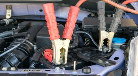 Car battery charger clamps connected to a battery inside a car engine compartment