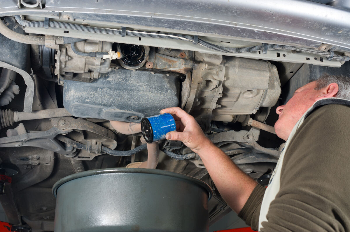 Mechanic under a lifted car removing an oil filter