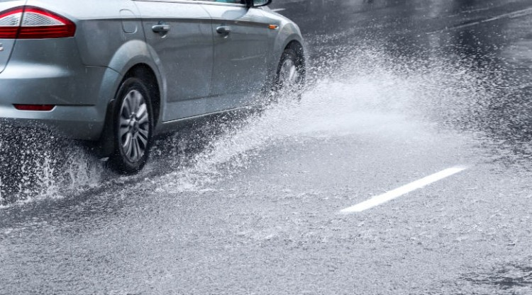 Side view of silver car driving in heavy rain