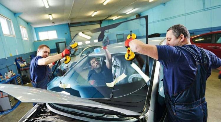 Workers in a garage repair shop replacing a car
