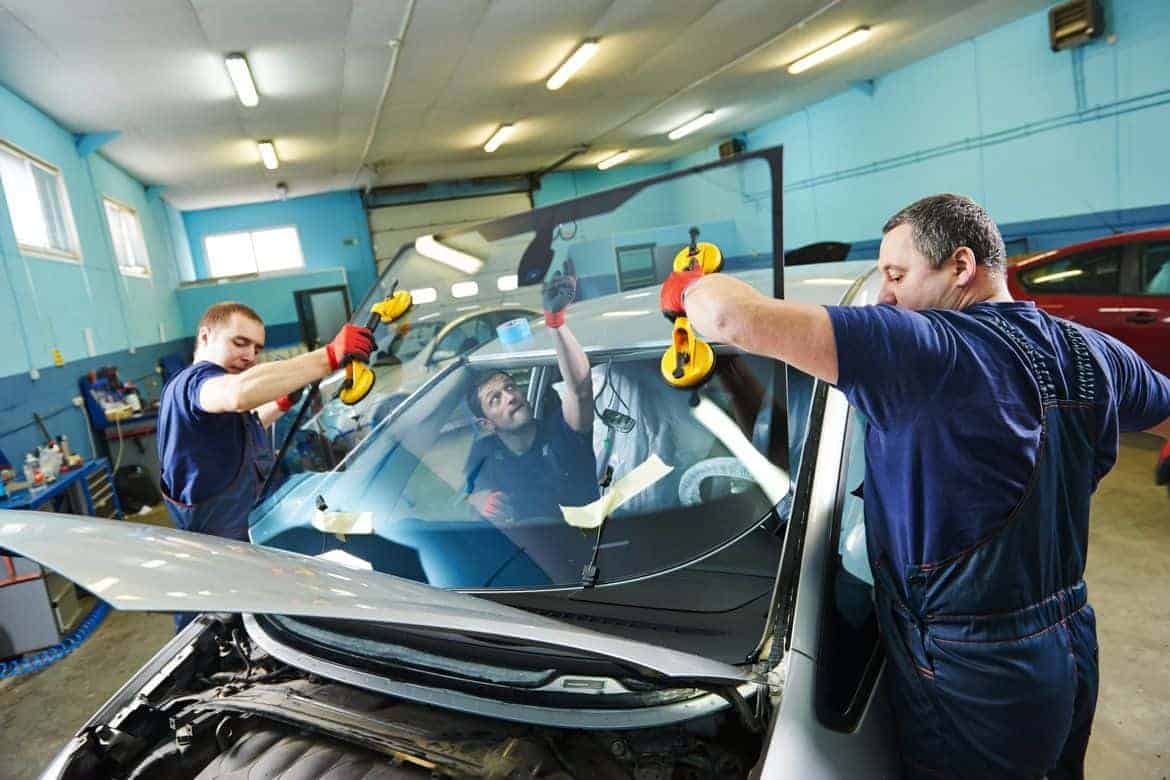 Workers in a garage repair shop replacing a car's windshield