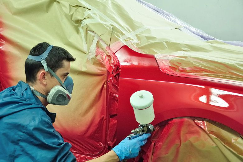 A man working on painting a red car