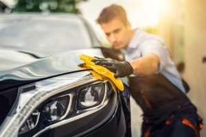 A man holding a microfiber cloth polishing a car after washing it