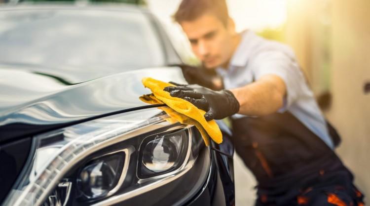 A man holding a microfiber cloth polishing a car after washing it