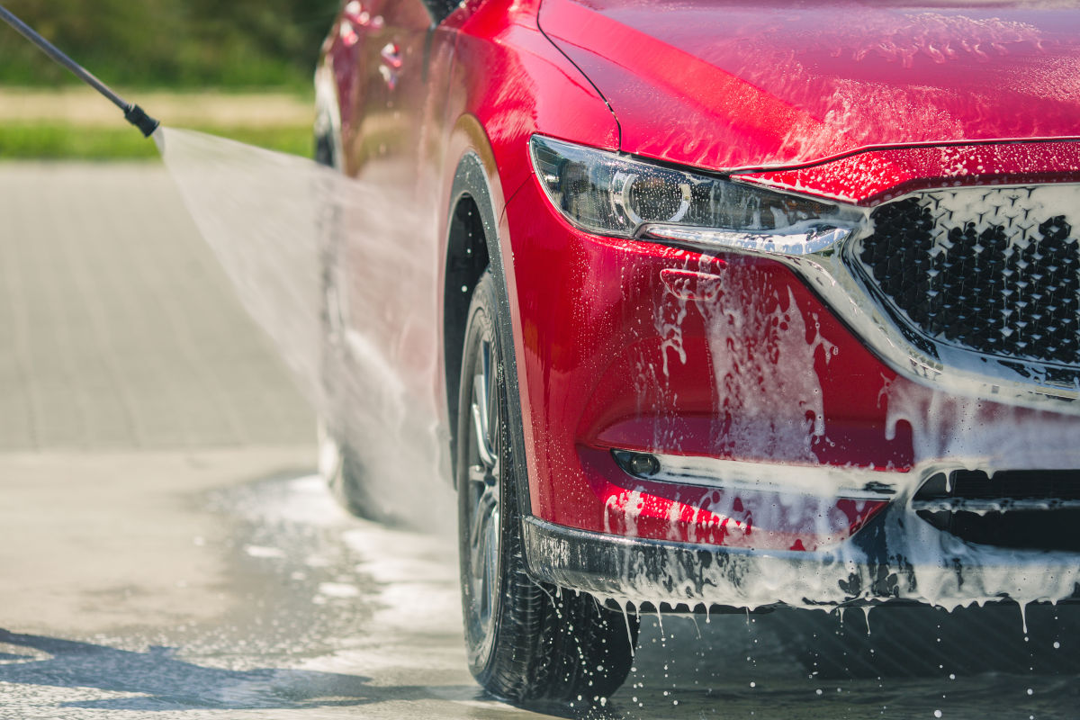 a parked red car being washed with a garden hose and soap