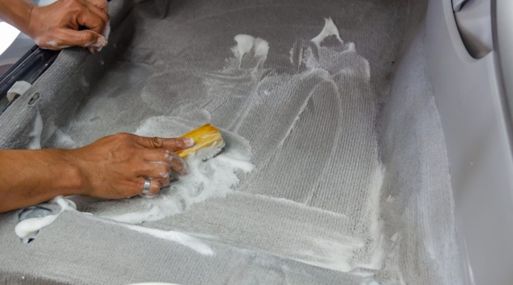 A man scrubbing a cars grey carpet with a yellow scrubbing brush