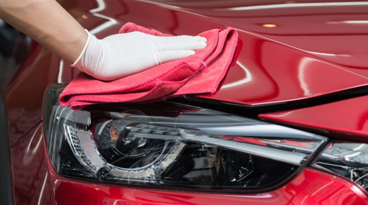 Mans gloved hand applying car paint sealant to the front end of a red car