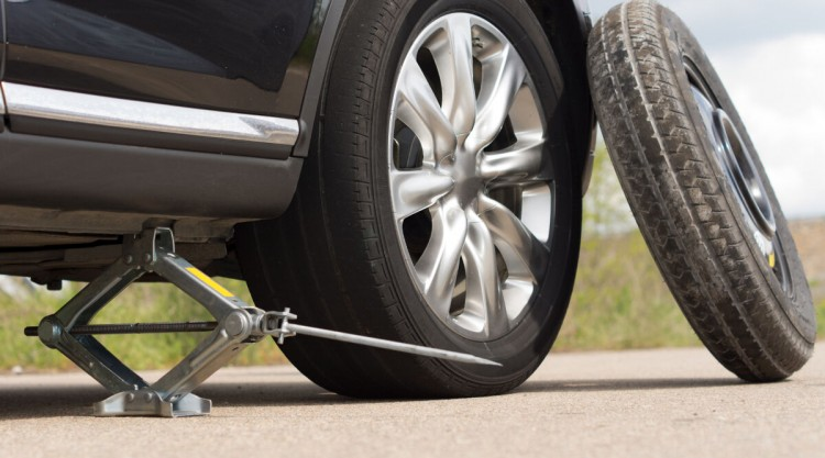 Scissor jack under a black car with a spare wheel beside it